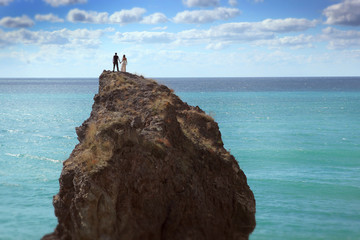Wedding bride and groom hold hands standing on rock in sea