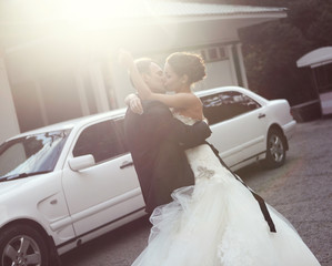 Couple kissing. The bride and groom near car limousine.