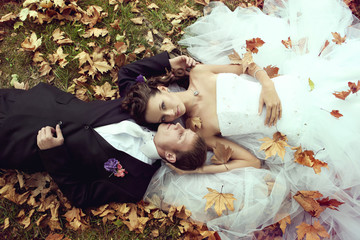 Wedding theme bride and groom are in maple leaves on grass