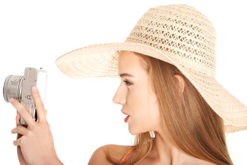 Portrait of a woman in hat taking photos