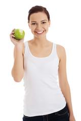 Happy brunette woman holding an apple
