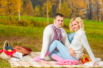 family picnic young couple in autumn park on the nature