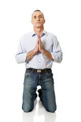 Mature man praying to God on knees