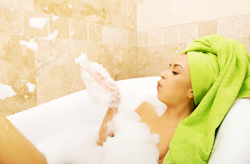 Woman blowing a foam in bath