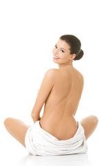 Back view nude woman sitting wrapped in towel