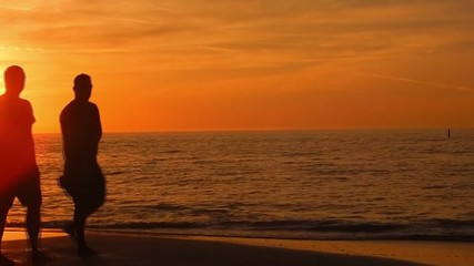 silhouettes of two men walking across beach during sunset
