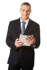 Happy mature man using digital tablet