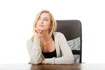 Happy woman sitting at the desk touching chin