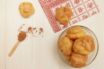 Pastry puffs  with wooden spoon of cacao powder