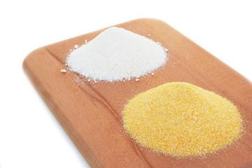 due farine per polenta su tagliere di legno_ sfondo bianco