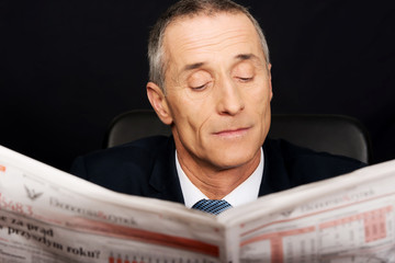 Businessman reading a newspaper in the office