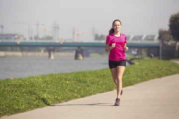 Young girl runs on Jogging track along the river.