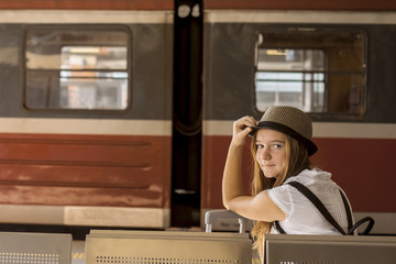 Young girl is waiting at the station a train. Travel concept.