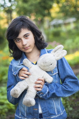 Young girl in a denim jacket with an old toy in the hands.