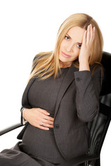 Tired pregnant woman sitting in the office