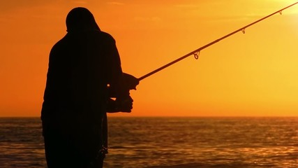 silhouette of dad teaching son how to fish in sunset