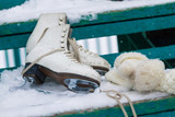 Skates and knitted mittens on a snowy bench