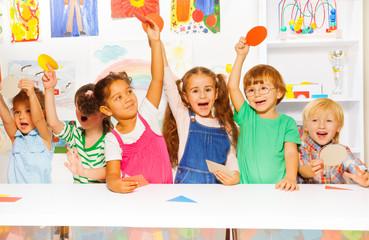Happy kids showing cardboard shapes