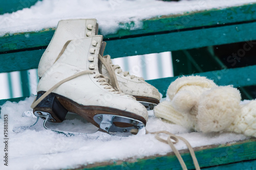 Fototapeta Skates and knitted mittens on a snowy bench