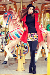 Fashion model posing on carousel in red coat