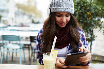 Happy young woman using tablet computer in a coffee shop