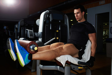 Athletic fit man doing workout legs exercise at gym
