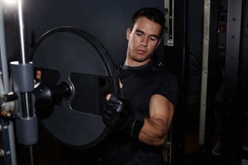 Muscular-build fit man changing weights of barbell