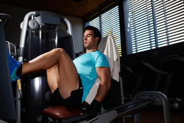 Professional bodybuilder exercising on legs press machine at gym