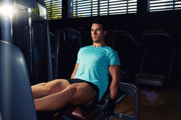 Attractive muscular build man exercising on press legs machinei