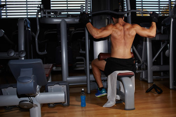 Back view of muscular build athlete exercising on press machine