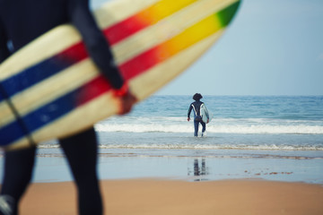 Professional surfers carrying their surfboards going to the sea