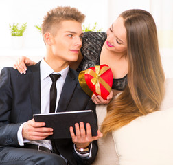 Valentine's Day. Happy woman giving a gift to her boyfriend