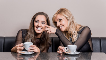Two smiling attractive women having a cup of coffee