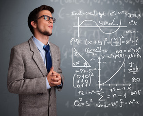 Handsome school boy thinking about complex mathematical signs