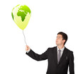 handsome man holding a green globe balloon