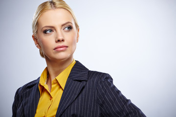 Portrait of a beautiful young business woman standing against bl
