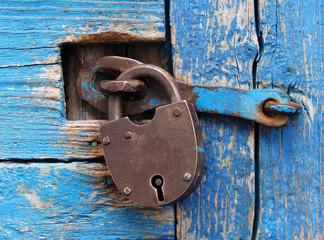 Rusty lock on a blue wooden door