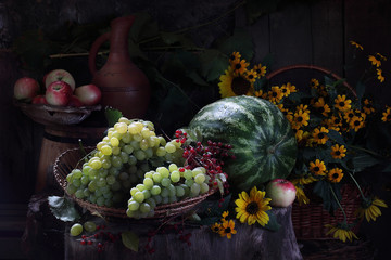 Water-melon, grapes, apple, red currant and bouquet from yellow