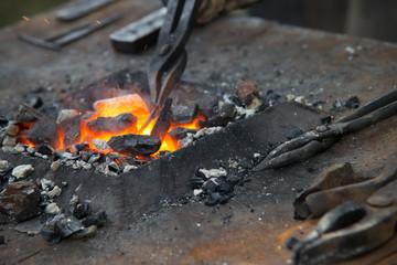 Blacksmith tools - pliers, hammer on the anvil feverish