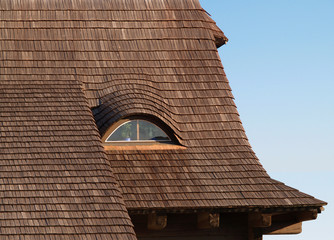 Traditional roof covered with shingles with window in an attic