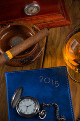wealthy man desk with cigars, vintage watch cognac and year plan