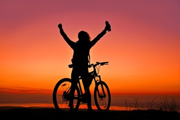 Biker-Girl at the sunset near lake