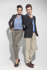 fashion couple posing on light grey background