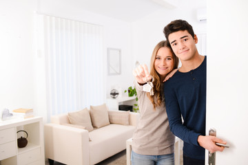 happy young couple in new house showing their keys