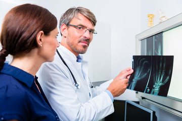Arzt mit Röntgenbild von Hand der Patientin