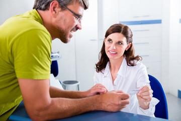 Patient an Empfang von Arztpraxis vereinbart Termin