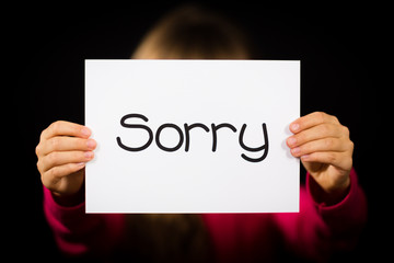 Child holding Sorry sign