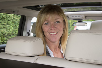 Portrait of a woman sitting in the rear seat of a car