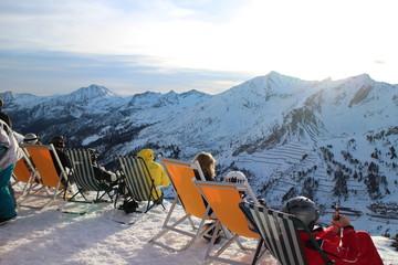 Skifahrer sonnen sich in Liegestuhl