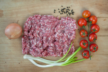 Raw minced meat with vegetables on a wooden table
